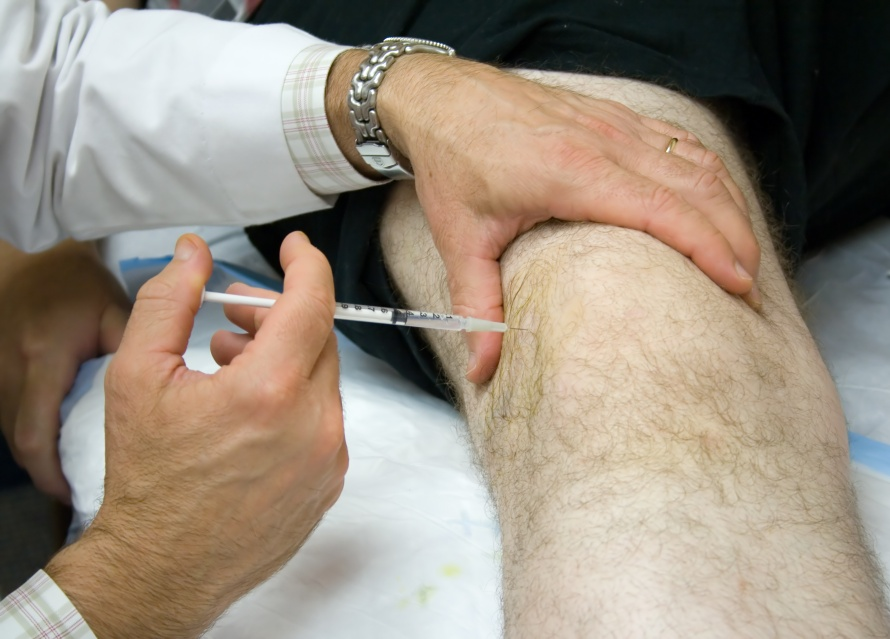 Doctor Giving Injection in the Knee of a Patient